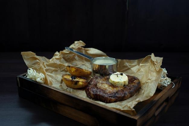Сочный стейк на гриле с маслом и кусочками запеченных баклажанов на винтажной доске стоит на деревянном столе