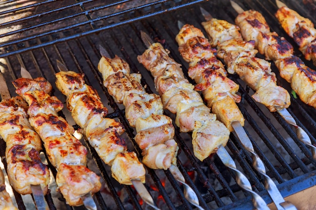 Grilled kebab cooking on metal skewer closeup. roasted meat cooked at barbecue.