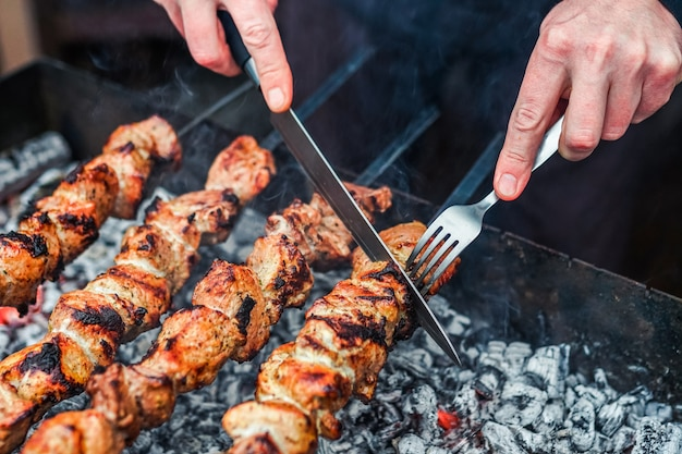 Grilled kebab cooking on metal skewer. roasted meat cooked at barbecue