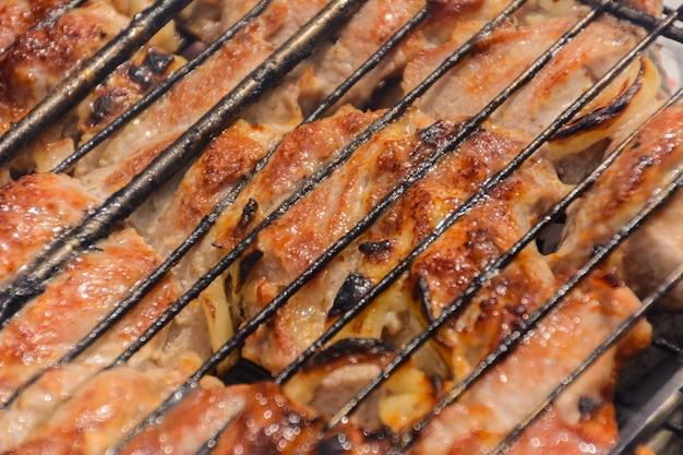 금속 그릴(그릴)에 구운 케밥 요리. 훈제 바베큐에서 구운 고기. 바베 큐 신선한 돼지고기 절단 조각을 닫습니다. 전통적인 동양 요리, 시시 케밥.