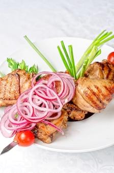 Жареное мясо кебаб с луком и помидорами на белой тарелке