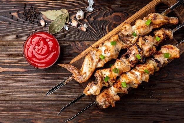 Жареный кебаб с кетчупом и специями на деревянных фоне.