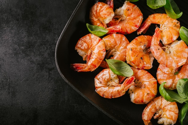 Grilled king prawns on pan on dark table