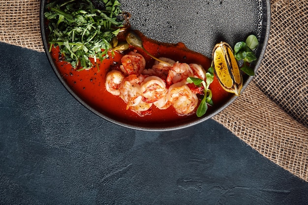 Grilled king tiger prawns with tomato sauce and arugula, beautiful serve from the chef, gray plate .