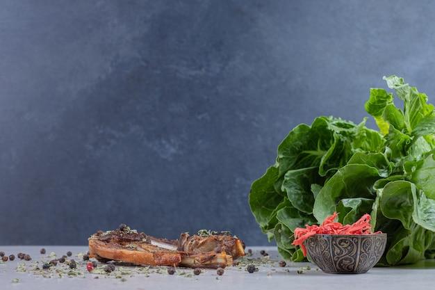 Жареные отбивные из баранины на белом фоне с салатом и имбирем.