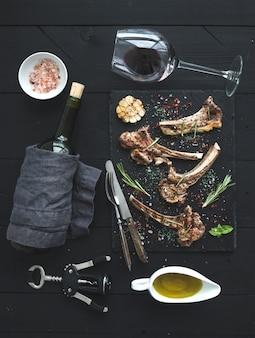 ラムチョップのグリル。子羊のラック、ニンニク、ローズマリー、スレートトレイのスパイス、ワイングラス、ソーサーとボトルのオイル
