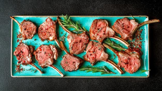 Жареные бараньи отбивные с розмарином на блюде бирюзового цвета, вид сверху, горизонтальный баннер