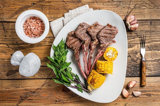 구운 양고기 스테이크는 옥수수와 토마토를 곁들인 접시에 담습니다. 나무 배경입니다. 평면도.