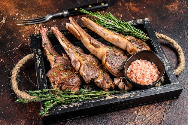 Grilled lamb chops steaks in a wooden tray
