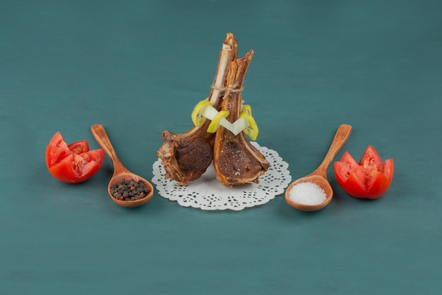 Grilled lamb chops with salt and pepper grains on blue table.