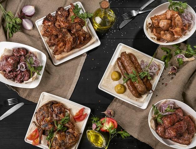 Grilled lamb kebab shashliks chicken tabaka and wings on black table