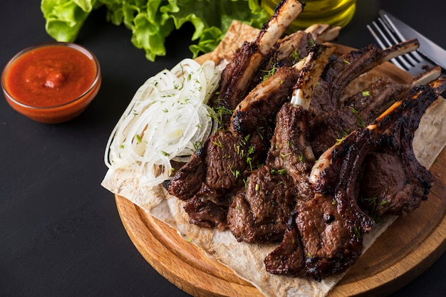 Grilled lamb meat on wooden board  red sauce.