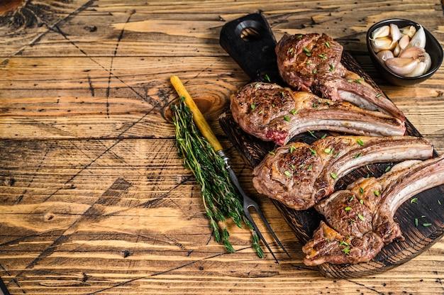구운 양고기 양고기 고기 커팅 보드에 스테이크를 볶습니다. 나무 배경입니다. 평면도. 공간을 복사하십시오.