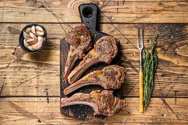 구운 양고기 고기는 커팅 보드에 스테이크를 자른다. 나무 배경입니다. 평면도.