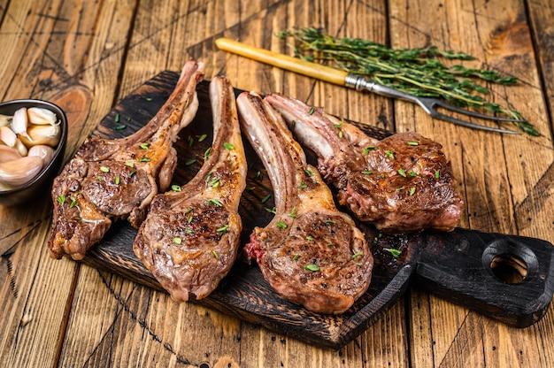 구운 양고기 양고기 고기 커팅 보드에 스테이크를 볶습니다.