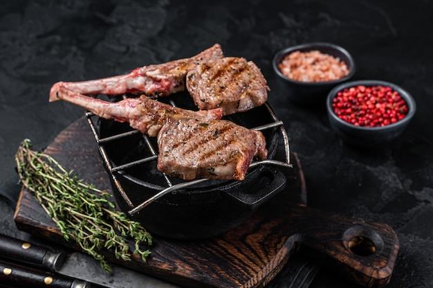 구운 양고기 고기는 그릴에 스테이크를 자른다. 검은 배경. 평면도.