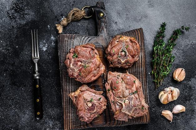 Стейки из мяса шеи ягненка на деревянной доске с зеленью