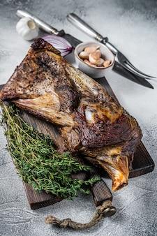 Жареное мясо ягненка или козьей лопатки на деревянной доске с ножом и вилкой для мяса