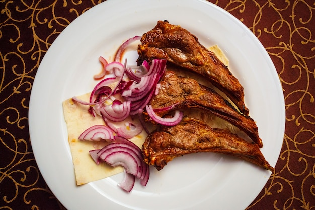Grilled lamb ribs on lavash bread with red onion.
