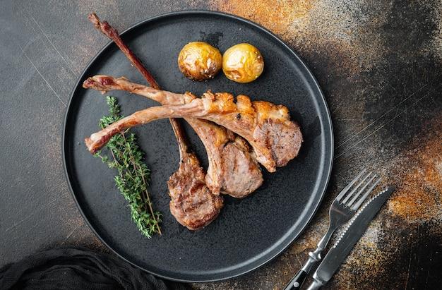 구운 양고기 갈비살 세트, 접시에, 오래된 어두운 전원풍 배경, 위쪽 전망 플랫 레이, 카피스페이스 및 텍스트 공간