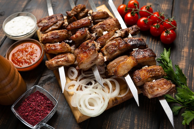 スパイスとソースを添えて串に刺したまな板の上のラムリブのグリル。暗い木製のテーブルの上から見る
