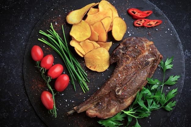 カッティングストーンボードにチップスと野菜を添えたラムステーキのグリル。