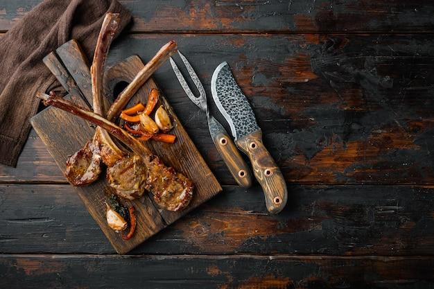 오래 된 어두운 나무 테이블에 나무 서빙 보드에 오렌지, 마늘, 당근 세트와 구운 양고기 스테이크, 평면도 평면 누워