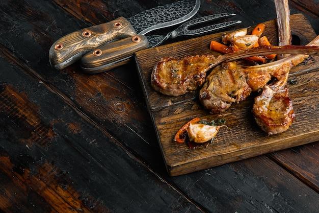 오래 된 어두운 나무 테이블에 나무 서빙 보드에 오렌지, 마늘, 당근 세트와 구운 양고기 스테이크