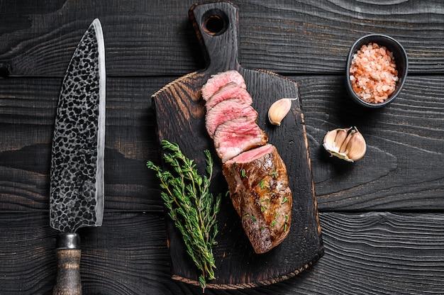 고기 칼에 구운 양고기 안심 고기 스테이크. 검은 나무 배경. 평면도.