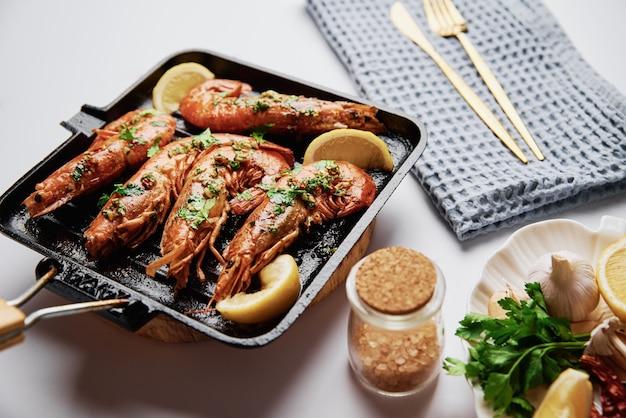 Большие креветки королевы на гриле с лимоном и специями на сковороде для гриля