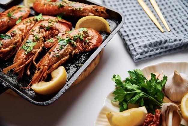 Большие креветки на гриле с лимоном и специями на сковороде-гриль