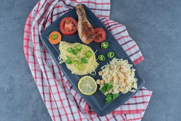 Нога-гриль, спагетти и рис на темной доске. Бесплатные Фотографии