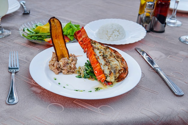 Grilled lobster is beautifully placed on a plate along with a side dish of mashed potatoes, fried banana, vegetables and rice and a glass of cocktail. expensive dinner at a restaurant