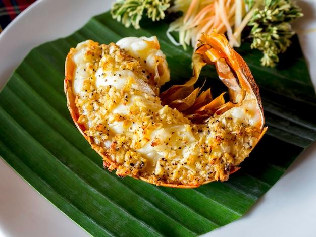 하얀 접시에 녹색 바나나 잎, 태국 스타일의 맛있는 해산물을 제공하는 마늘 버터에 뿌린 구운 랍스터 꼬리. 프리미엄 사진