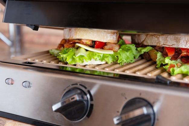 Запеченный на гриле длинный сэндвич или панини на мангале электрогриля. хрустящий хлеб, листья салата, помидоры, чеддер, соус сальса - ингредиенты для быстрой еды дома на пикнике, завтраке или перекусе.