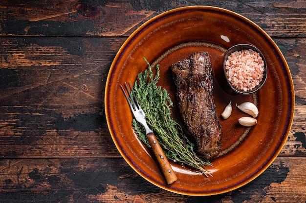 Жареный стейк из говядины с юбкой мачете на деревенской тарелке с травами и розовой солью. темный деревянный фон. вид сверху. скопируйте пространство.