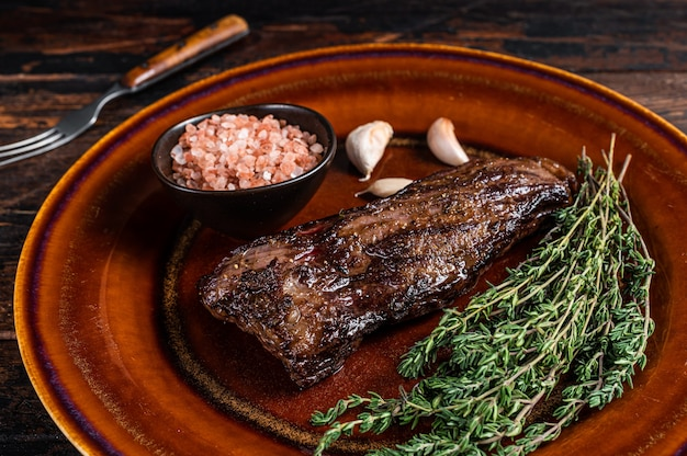 Жареный стейк из говядины с юбкой мачете на деревенской тарелке с травами и розовой солью. темный деревянный фон. вид сверху.