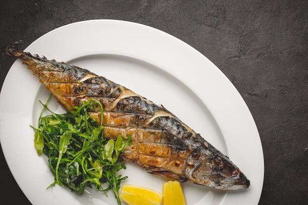 Grilled mackerel fillets with lemon on black board