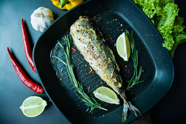 Grilled mackerel in a grill pan. proper nutrition. dark background.