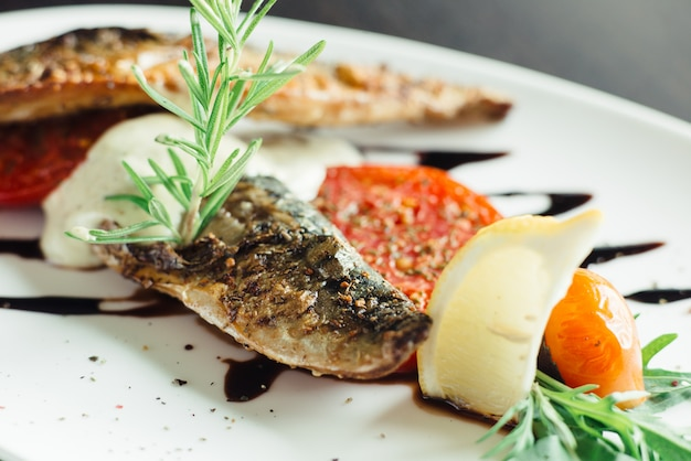 Grilled mackerel with onion on white plate on wooden table