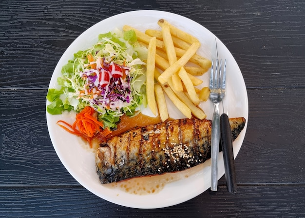 Grilled mackerel with salad and french fries on wooden background