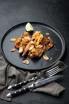 グリルしたマンゴーエビまたはエビのセット、プレート、黒いテーブル
