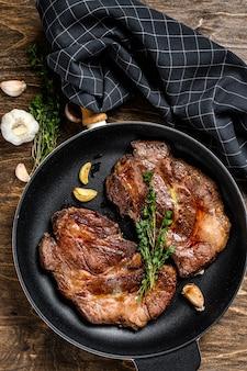 Grilled marble meat steaks chuck eye roll in a pan