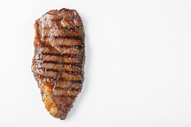 Grilled marbled beef steak striploin isolated on white background, top view with copy space