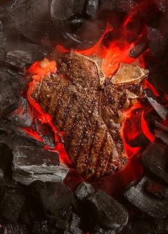 Grilled marbled beef steak with coals and smoke