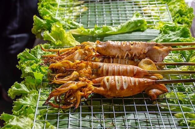 스틸 그릴에 해물 소스와 야채를 곁들인 절인 오징어 구이