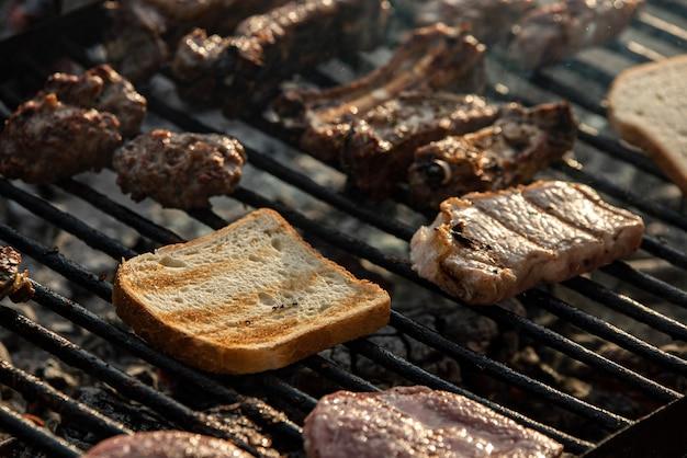 グリルした肉とパンのディテール、グリルで調理 Premium写真