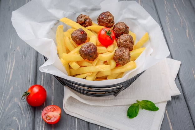Grilled meat balls with french fries on wooden table