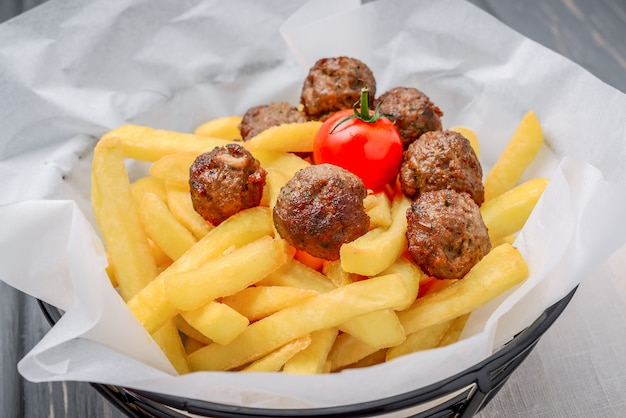 Grilled meat balls with french fries on wooden