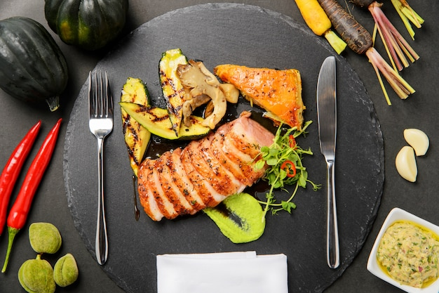 Grilled meat on black stone board with vegetable
